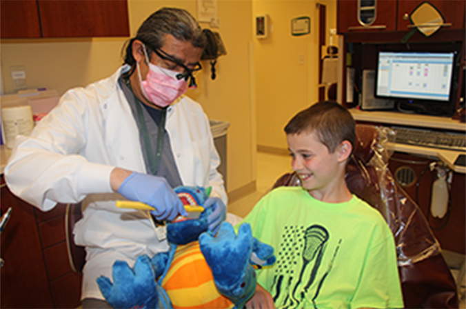 Doctor teaching kid how to use a toothbrush